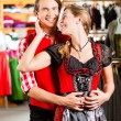 Couple is trying Dirndl or Lederhosen in a shop — Stock Photo #71689617