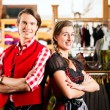 Couple is trying Dirndl or Lederhosen in a shop — Stock Photo #71689667