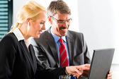 Businesspeople looking at laptop in consultation — Stock Photo