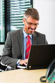 Businessperson with laptop in his business office — Stock Photo