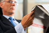 Boss in his office reading newspaper — Stock Photo
