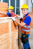 Builder sawing a wood board of building — Stock Photo