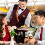 Waiter serving dinner in elegant restaurant — Stock Photo #77909016