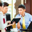 Business people at meeting in hotel lobby — Stock Photo #77909232