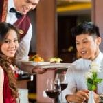 Waiter serving dinner in elegant restaurant — Stock Photo #77909350