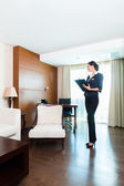 Executive housekeeper controlling hotel room — Stock Photo