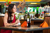 Chinese woman waiting in restaurant for date — Stock Photo