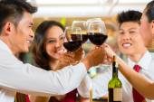 Chinese couples toasting with wine in restaurant — Stockfoto