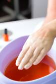 Woman in nail salon having paraffin bath — Stock Photo