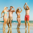 Friends jumping on ocean beach in vacation — Stock Photo #79097508