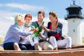 Friends drinking bottled beer at beach — Stock Photo