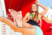 Woman in wicker bench chair drinking cocktail — Stock Photo