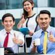 Asian businesspeople working outside with coffee — Stock Photo #79106324
