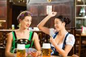 Friends drinking beer in Bavarian pub playing cards — Stock Photo