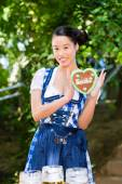 Asian Woman with Bavarian gingerbread heart — Stock Photo