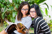 Two Asian girlfriends reading magazine — Stock Photo