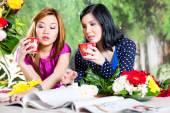 Two Asian girlfriends with fashion magazine — Stock Photo