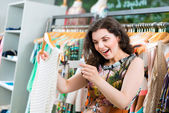 Young woman shopping in fashion department store — Stock Photo