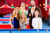 Family playing pool billiard game — Stock Photo
