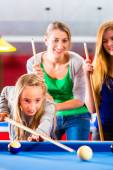 Girl playing pool billiard with family — Stock Photo