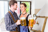 Brewer and woman toasting in beer brewery — Stock Photo