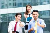 Asian businesspeople working outside with coffee — Stock Photo