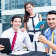 Asian businesspeople working outside with coffee — Stock Photo #79115184