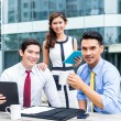 Asian businesspeople working outside with coffee — Stock Photo #79115212