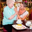 Granny and granddaughter laughing in cafe — Stock Photo #79202032