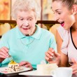 Senior woman and granddaughter at coffee in cafe — Stock Photo #79202086
