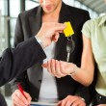 Dealer handing woman auto key — Stock Photo #79207472