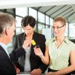Dealer handing woman auto key — Stock Photo #79207474