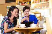 Mujeres jóvenes en una tienda de café asiática — Foto de Stock