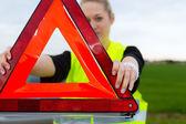Mujer joven con triángulo de advertencia en la calle — Foto de Stock