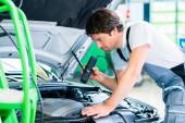 Mechanic with diagnostic tool in car workshop — Stock Photo