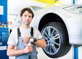 Mechanic tire change in car workshop — Stock Photo