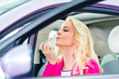 Woman doing her makeup in car — Stock Photo