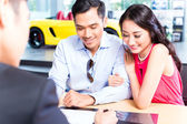 Couple signing sales contract for car at dealership — Stock Photo