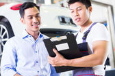 Car mechanic and customer in auto workshop — Stock Photo
