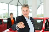 Man with woman and auto in car dealership — Stock Photo