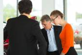 Man with couple and auto in car dealership — Stock Photo