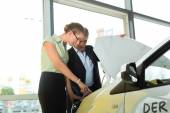Man and woman in car dealership looking under  a hood — Stock Photo