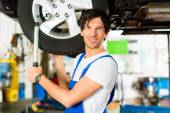 Young mechanic working on car — Stock Photo