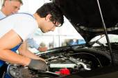 Man and mechanic looking at car engine — Stock Photo
