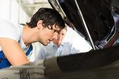 Man and car mechanic looking beneath a hood — Stock Photo