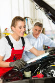 Man and female car mechanic in workshop — Stock Photo