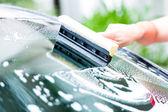 男子清洗挡风玻璃同时洗车 — 图库照片