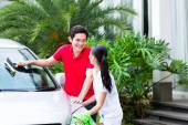 Asian couple cleaning together car — Stock Photo