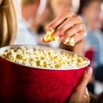 Girl eating popcorn in cinema — Stock Photo #79216310