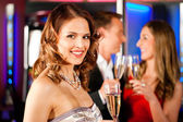 Three friends with champagner in a bar — Stock Photo
